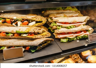sandwiches stuffed with ham and tomato for sale in a bakery shop