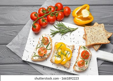 Sandwiches with tasty cream cheese and vegetables on table