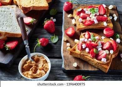 sandwiches of toasted bread with peanut butter, sliced strawberries and marshmallow on a wooden cutting board on an old rustic table, cllose-up