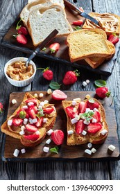 sandwiches of toasted bread with peanut butter, sliced strawberries and marshmallow on a wooden cutting board on an old rustic table, vertical view