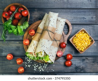 Sandwiches twisted roll Tortilla burritos three pieces on a wooden cutting board on a gray background, lettuce, cucumbers malosollnye, cherry tomatoes, corn, onion rings, meat, top view