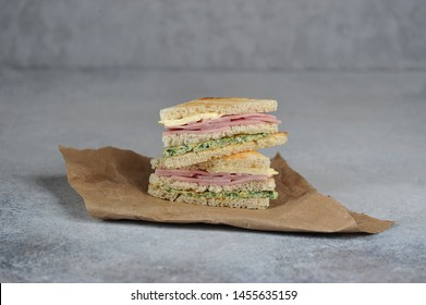 Sandwiches of white bread on Kraft paper. Sandwich stuffing consists of ham, cheese and scrambled eggs with spinach.