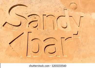 Sandy bar written in the sand on the beach