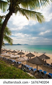 sandy bay with coconut palms and straw beach umbrellas many people