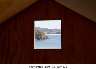 Sandy Bay, New Zealand - October 26 2019: Clever design of holiday home shows window acting as a framed painting or photograph. View of Whananaki from Sandy Bay. Basic building materials, great space.