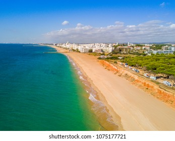Sandy beach along cliffs and RVs in touristic resorts of Quarteira and Vilamoura, Algarve, Portugal