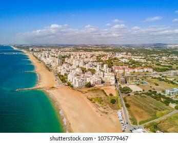 Sandy beach along cliffs and RVs in touristic resorts of Quarteira and Vilamoura, Algarve, Portuga