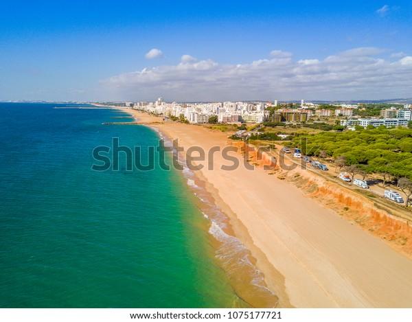 Sandstrand entlang von Felsen und RVs in touristischen Resorts von Quarteira und Vilamoura, Algarve, Portugal