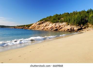 Sandy beach along the coast of Maine with blue sky