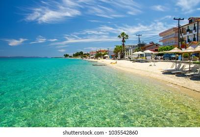 Sandy beach with blue paradise water of Toroneos kolpos gulf, blue sky, white clouds in Pefkohori, Halkidiki, Kassandra, Macedonia, Greece