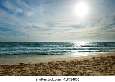 Sandy beach and blue sea at sunset. Beautiful sea landscape. The sea a bright turquoise colour, the sky the setting sun and blue sky with white clouds. Atlantic ocean, Spain