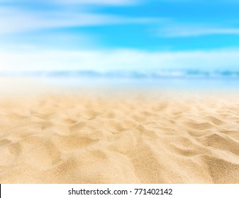Sandy beach with blurry blue ocean