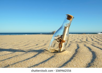 sandy beach with a bottle with a magic message at sunset