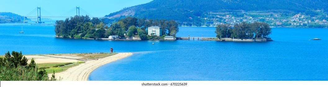 Sandy beach in Cesantes town and San Simon island (Galicia, Spain). Summer Ria de Vigo landscape. Three shots stitch panorama.