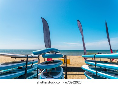 Sandy beach, color kayaks based on stand, in background beautiful view on blue ocean, sunny day