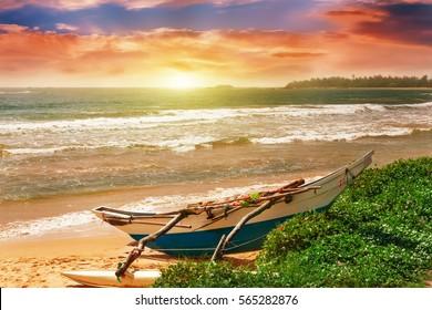 Sandy beach with colorful fishing boat at sunset. Sri Lanka Island.