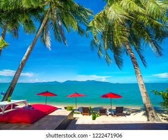 Sandy beach in day time is beautiful and peaceful.Sunbed with red umbrella in  tropical calm beach and palm trees or coconut trees at Maenam beach over looking Koh Koh Phangan Koh Samui Surat Thani
