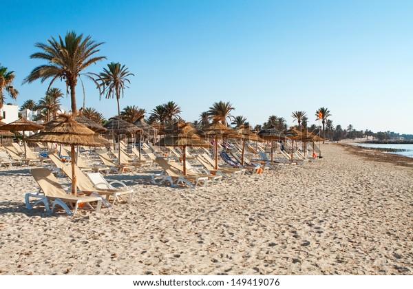 Sandstrand mit Liegestühlen und Sonnenschirmen bei Sonnenuntergang