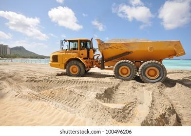 Sandy beach with a dump trunk full of sand