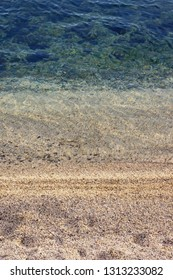 Sandy beach at the edge of the water, striped background