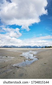Sandy beach at Gustavus Alaska with clouds at low tide.