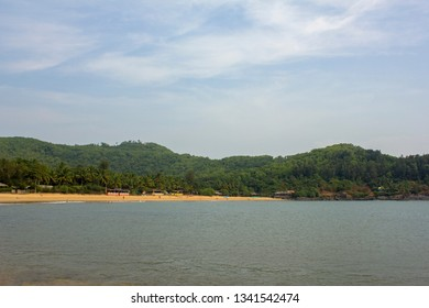 sandy beach with hills, green palm trees and huts, view from the sea