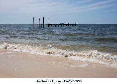 Sandy beach with light waves and sea birds perched on horizon with wooden pylons in the Gulf of Mexico.  Blue sky, blue ocean waves and wooden structures in the water with light surf