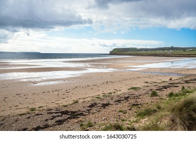 Sandy beach at low tide on a partly cloudy spring day. Two people with a dog walking along the shore are visible in distance.