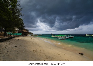Sandy beach with moored Indonesian boats on the tropical island of Gili Meno. Heavy leaden clouds hung over the beach, a thunderstorm is approaching.
