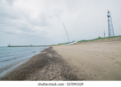 Sandy beach on a rainy day in cloudy weather with sailing yacht