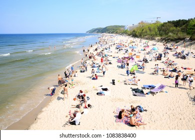 Sandy beach and people in Miedzyzdroje, Pomerania, Poland, 04-30-2018 at 1pm