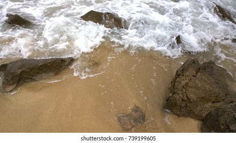 Sandy beach with rocks covered by a wave