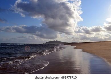 Sandy beach, rocks, sea, clouds. Cape Isle Fake. Primorye. Russia.