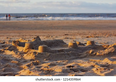 Sandy beach with sandcastle and panoramic view of sea coast during warm sunset