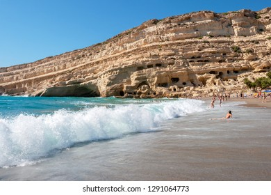 Sandy beach and sandstone cliffs with caves at Matala. South coast, Iraklion Province, Crete, Greece