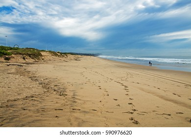 Sandy beach shoreline and vegetated dunes against blue skyline in Durban, South Africa