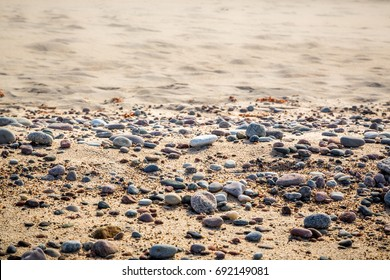 Sandy beach with small pebbles and smoth water, selective focus.