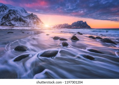 Sandy beach with stones in blurred water, colorful pink with blue clouds sky and snowy mountains at sunset. Utakleiv beach, Lofoten islands, Norway. Winter landscape with sea, waves, rocks at twilight