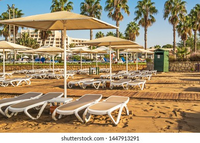 Sandy beach with sun beds and umbrellas on coast of Turkey. Turkey, Belek. September 12, 2017