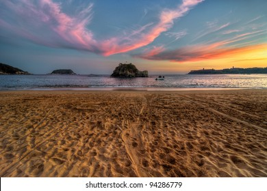 Sandy beach sunset with dramatic clouds