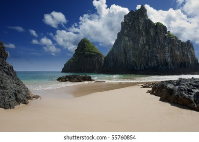 Sandy beach surrounded by rocks taken against deep blue skies covered with few clouds. Picture is taken on Fernando de Noronha Island, Brazil.