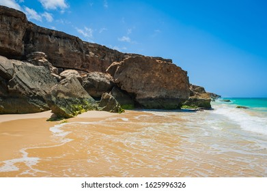 Sandy beach surrounded by rocky cliffs eroded by Atlantic Ocean water waves and wind. Scenic landscape the West coast of Boa Vista island, Cape Verde.