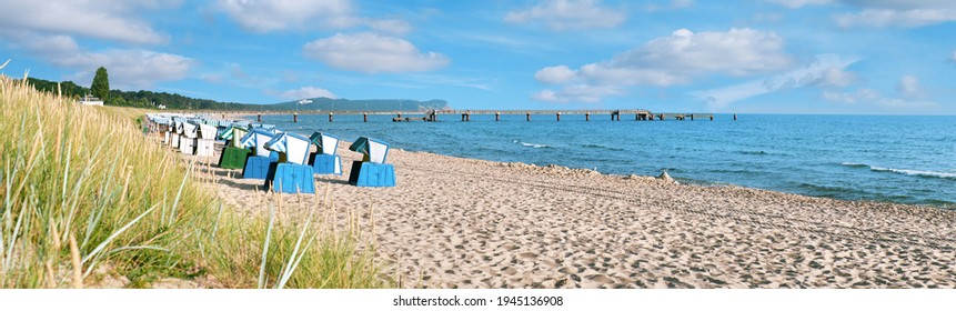 Sandy beach and traditional wooden beach chairs on island Rugen, Northern Germany, on the coast of Baltic Sea. Panorama image