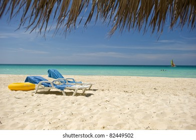 Sandy beach of tropical resort with umbrellas and two chairs