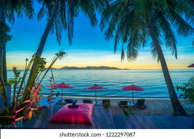 Sandy beach in twitlight time is beautiful and peaceful.Sunbed with umbrella in  tropical calm beach and palm or coconut trees at Maenam beach over looking Koh Pha ngan Koh Samui Surat Thani Thailand.