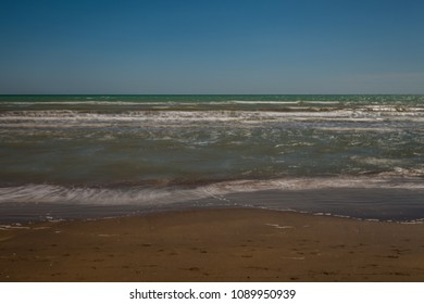 Sandy beach with waves and undertow, Bibione, Veneto, Italy