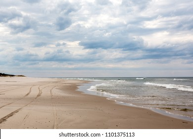 Sandy beaches by the Baltic sea in Poland with dramatic sky in the background.