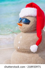 Sandy christmas snowman in red santa hat and sunglasses at sunny beach. Holiday concept for New Years Cards.