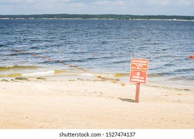 """sandy city beach with small waves and buoys. plates with inscriptions in Russian: """"carefully! sharp increase in depth, 20 meters"""" and """"swimming is prohibited"""". water safety measures"""