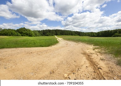 Sandy country road through the field. summer landscape with blue sky and clouds above the ground